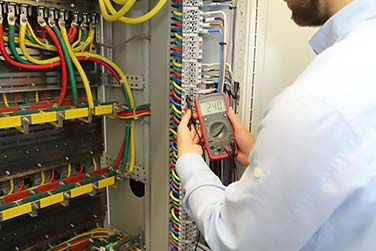 Electrician is working in electrical cables distribution fuse box with multimeter